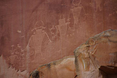 Petroglyphs of the Anasazi Native American people on red sandstone wall in Capitol Reef National Park, Utah