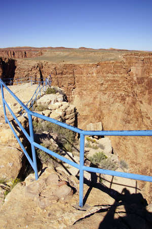 Flimsy blue rail overlooking  the rim of the Little Grand Canyon of the Colorado River, Arizona