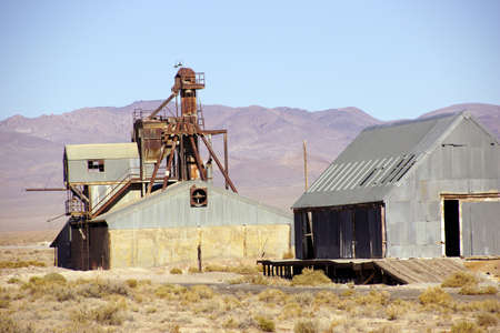 rusting: Old mining buildings, rusting in the desert,with mountains in background, Nevada