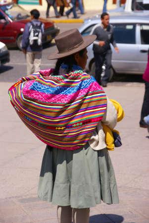 quechua: CUSCO PERU 29 AUG 2008 - Quechua Indian woman with colorful backpack,  Cusco, Peru, South America