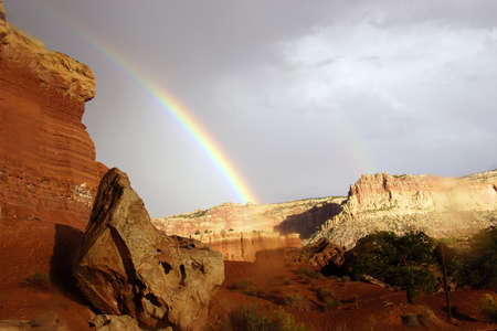 Rainbow and brief dramatic sunshine before sunset,  on cliffs in Capitol Reef National Park, Utah  Reklamní fotografie