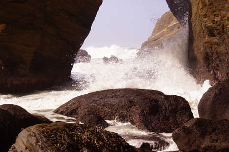 Surf breaking on entrance to Devils Punch Bowl near Otter Rock, Oregon coast   Stock Photo