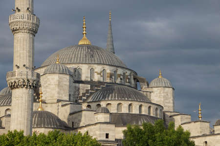 camii:  Sultan Ahmet Camii ( Blue Mosque ) glows in early evening light against dark clouds in the background  in Istanbul, Turkey
