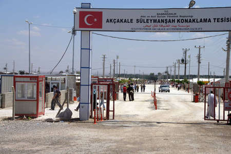 syrian: AKCAKALE, TURKEY - Jun 8, 2014 - People enter the Akcakale Syrian  refugee camp near the Syrian border,  in Southeastern Turkey, June 2014
