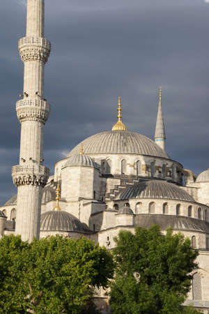 camii:  Sultan Ahmet Camii ( Blue Mosque ) glows in early evening light against dark clouds in the background  in Istanbul, Turkey  Stock Photo