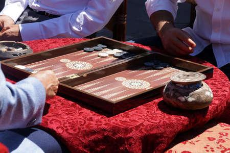 Two men enjoying a game of backgammon  tavla