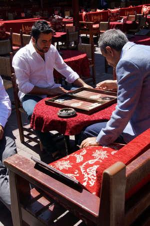 Two men enjoying a game of backgammon  tavla       Editorial