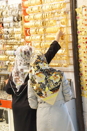 Women with scarves choosing golden bracelets  in the bazaar of  Bursa, Turkey   Редакционное