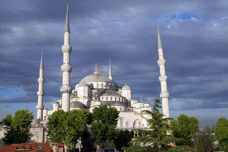 glows:  Sultan Ahmet Camii ( Blue Mosque ) glows in early evening light against dark clouds in the background  in Istanbul, Turkey  Stock Photo