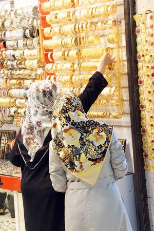 sciarpe: Le donne con sciarpe scegliendo braccialetti d'oro nel bazar di Bursa, Turchia