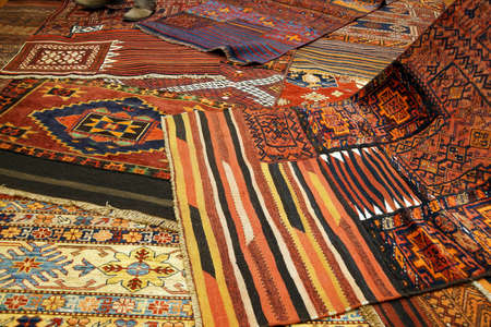 red carpet background: Overlapping carpets with intricate Kurdish  patterns in rug store  in Istanbul, Turkey