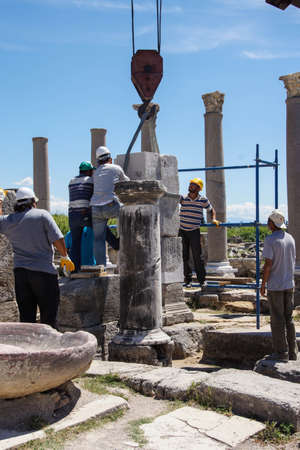 PERGE, TURKEY - JUN 2, 2014 - Workers use modern equipment to restore ancient columns in  Perge,  Turkey   Editorial