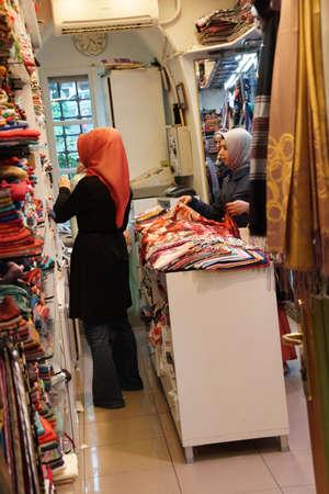 BURSA, TURKEY - MAY 22, 2014 - Women with scarves choosing clothing in the bazaar of  Bursa, Turkey