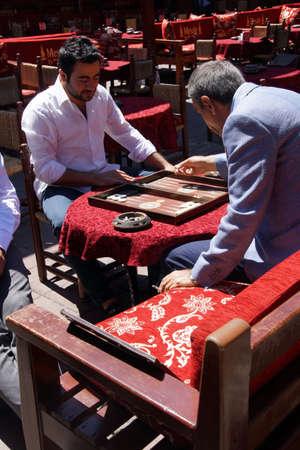 ISTANBUL, TURKEY - MAY 16, 2014 -Two men enjoying a game of backgammon (tavla) in a teahouse  in Istanbul, Turkey  Editorial