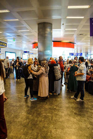 guides: ISTANBUL, TURKEY - MAY 15, 2014 -Arriving passengers run the gauntlet of travel guides as they exit customs area of the airport  in Istanbul, Turkey