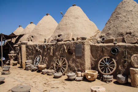 Traditional beehive mud brick houses with farm tools, Harran near the Syrian border, Turkey