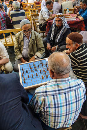 tea house: URFA, TURKEY - JUN 8, 2014 - Typical tea house scene with men playing boardgames and talking  in Urfa bazaar,  Turkey