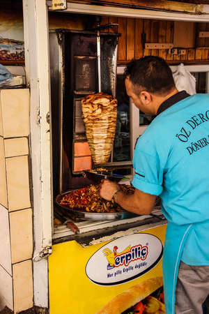 kabab: URFA, TURKEY - JUN 7, 2014 - Cook slices shawarma from the spit for doner kababs  in Sanliurfa,  Turkey