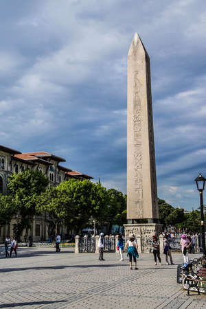 ISTANBUL, TURKEY - MAY 16, 2014 -Tourists walk by the Egyptian obelisk in the ancient site of the Hippodrome   in Istanbul, Turkey