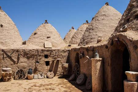 mud house: Traditional beehive mud brick houses with farm tools, Harran near the Syrian border, Turkey