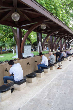 BURSA, TURKEY - MAY 22, 2014 - Men perform ablutions before afternoon prayer at the Ulu Cami  in the bazaar of  Bursa, Turkey