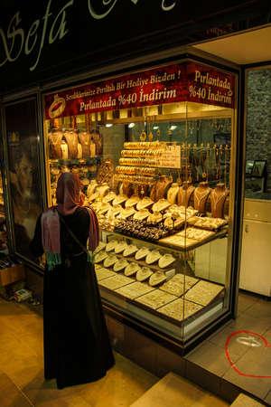 BURSA, TURKEY - MAY 22, 2014 - Women with scarves choosing gold bracelets  in the bazaar of  Bursa, Turkey Редакционное
