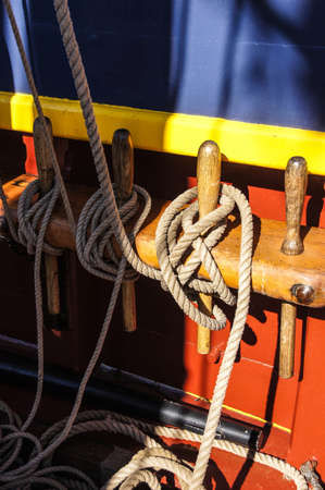 bulwark: Coiled rope lines stored on belaying pins  on a wooden tall ship Stock Photo