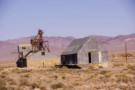 rusting: Old mining buildings, rusting in the desert,with mountains in background, Nevada Stock Photo