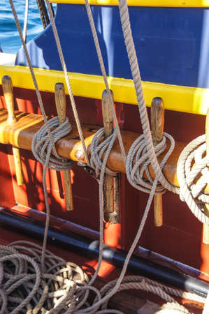 belaying: Coiled rope lines stored on belaying pins  on a wooden tall ship Stock Photo