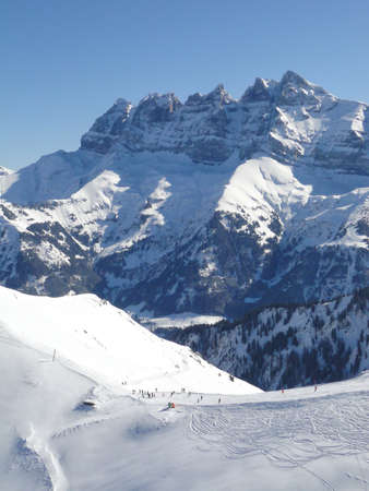 soleil: Skiers drop down into the valley  with the Dents du Midi in the background, Portes du Soleil, Switzerland