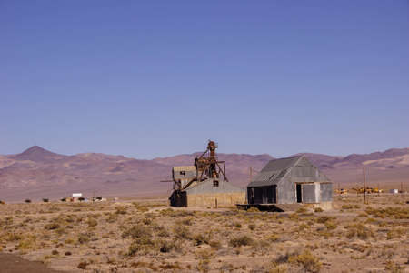 rusting: Old mining buildings, rusting in the desert,with mountains in background, Nevada Editorial