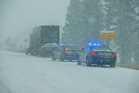 Politieauto's stoppen om een ??grote vrachtwagen te assisteren tijdens een winterstorm in Oost-Oregon