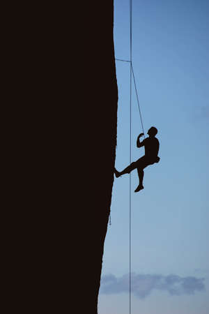 smith rock: Silhouette of climber on sheer cliff of Monkey Face, Smith Rock State Park, Central Oregon