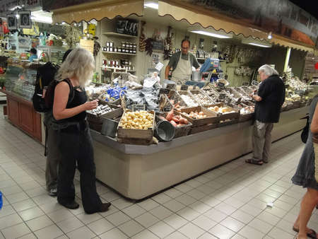 browses: AVIGNON, FRANCE - OCT 2, 2011 - Shopper browses the vegetables   in Les Halles, Avignon, France Editorial