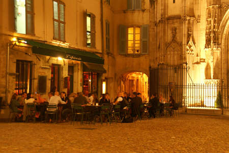 AVIGNON, FRANCE - SEP 30, 2011 -  Casual diners enjoy an evening meal near an old church on Sep 30, 2011  in Avignon, France