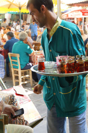 teahouse: URFA, TURKEY - JUN 8, 2014 - Waiter brings drinks in  tea house  in Urfa bazaar,  Turkey