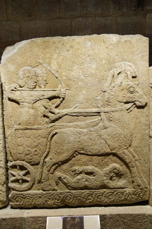 ANKARA, TURKEY - MAY 21, 2014 -  Chariot with driver and archer. Orthostat stele from Kargama about 800 BCE,  Ankara, Turkey