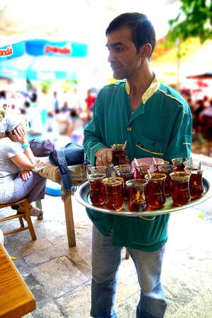 tea house: URFA, TURKEY - JUN 8, 2014 - Waiter brings drinks in  tea house  in Urfa bazaar,  Turkey