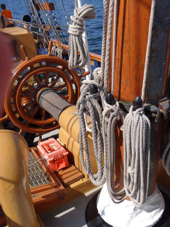 ketch: Coiled rope lines stored on belaying pins  on a wooden tall ship Stock Photo