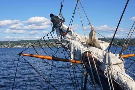 jib: Sailor walks out on the bowsprit to furl the jib sailof tall ship  near Kirkland, Washington Editorial
