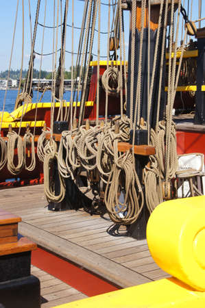 belaying: Coiled rope lines stored on belaying pins  on a wooden tall ship Editorial