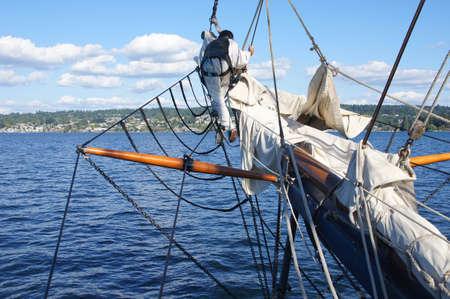 einrollen: Sailor Spazierg�nge auf dem Bugspriet, um die Ausleger sailof Gro�segler in der N�he von Kirkland, Washington furl