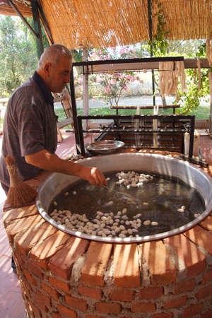 unwinding: EPHESUS, TURKEY - MAY 25, 2014 - Boiling silkworm cocoons before unwinding silk,  Ephesus, Turkey