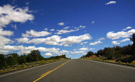 partly: Desert highway with horizon and blue skies, partly cloudy, Arizona