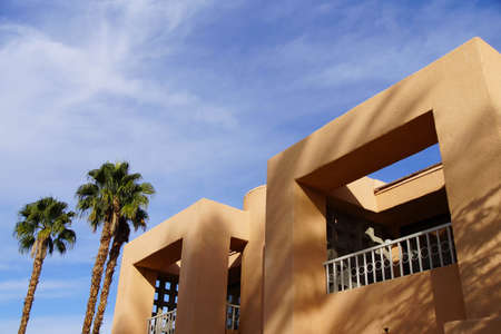 a mirage: Palm tree and Southwestern architecture, spanish adobe style building with blue desert sky,  Rancho Mirage, California Stock Photo
