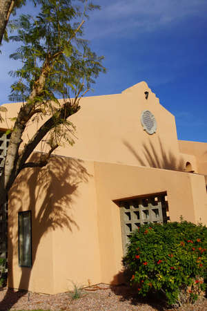 southwestern: Palm tree and Southwestern architecture, spanish adobe style building with blue desert sky,  Rancho Mirage, California Stock Photo