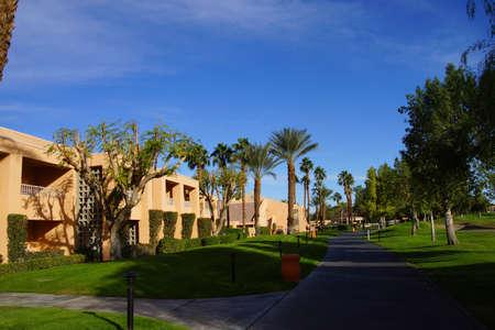 southwestern: RANCHO MIRAGE, CALIFORNIA - DEC 20, 2014 - Southwestern style hotel buildings in green oasis with Palm trees,  Rancho Mirage, California