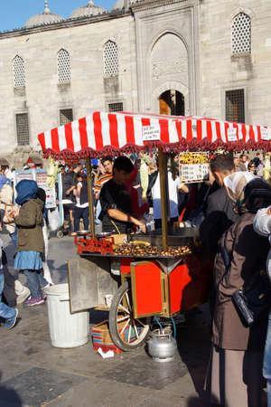 street vendor: ISTANBUL, TURKEY - MAY 17, 2014 - A street vendor sells roasted chesnuts  near the Galata Bridge in Istanbul,  Turkey