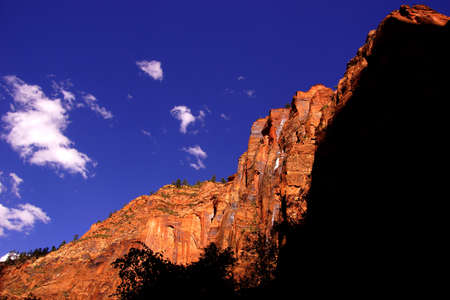 steep cliff: Shadows define the steep cliff faces of Mount SinewavaZion National Park, Utah Stock Photo