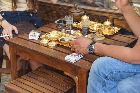 tea service: SIRINCE, TURKEY - MAY 25, 2014 - Young couple smoke cigarettes while having afternoon tea service, Sirince, Turkey